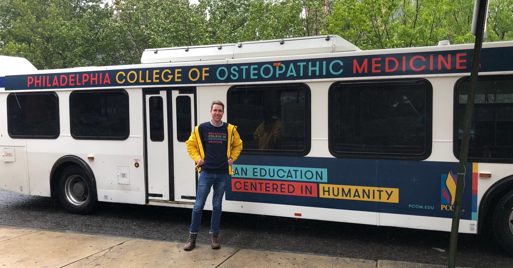 Student wearing PCOM swag posing in front of SEPTA bus with PCOM ad.