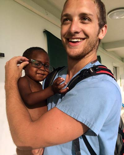 Luke King (DO '18) holding an infant during a medical mission trip to Haiti