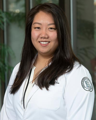 Professional headshot photograph ofHannah Shin, DO '19, weaing her student physician white coat