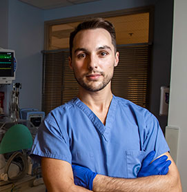 Photograph of Dustin Flannery, DO '11 working in his blue scrubs in the neonatal intensive care unit (NICU)