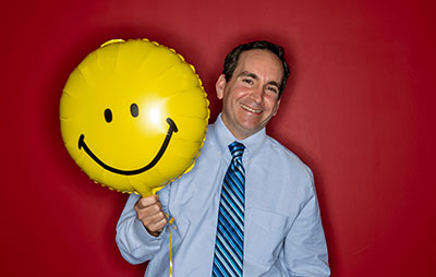 Scott Glassman, PsyD '13, poses with a smiley face balloon.