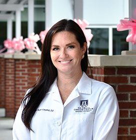 Alicia Huff Vinyard, DO '11, smiling in her white coat in front of a medical facility.