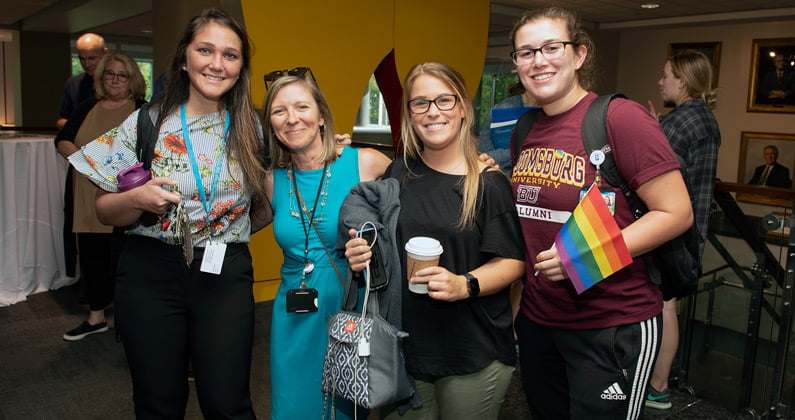 Group of 4 female students and faculty smile while holding pride flags at the 2019 LGBTQIA Welcome Reception event