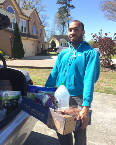 Kedron Spence (DO '22) getting groceries out of his car in a Gwinnett County neighborhood.