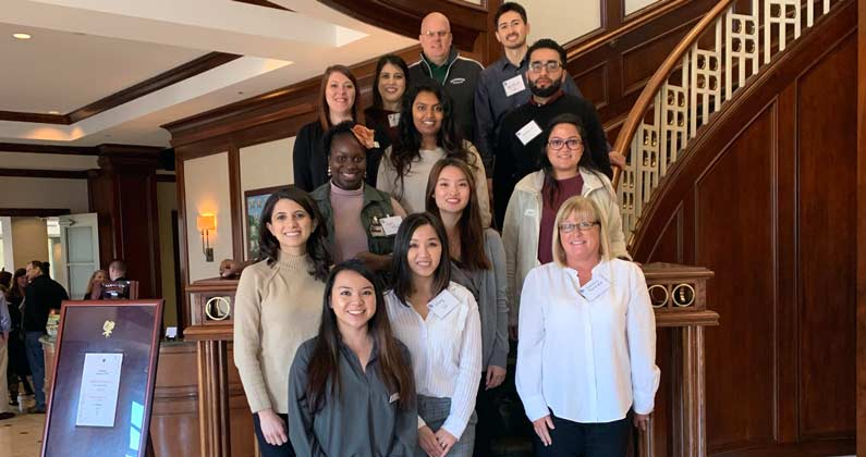 PCOM Georgia students, alumni and faculty take a group photograph on a staircase at the GSHP Committee Day.