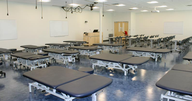 Physical therapy classroom at GA-PCOM with examination tables and educational equipment
