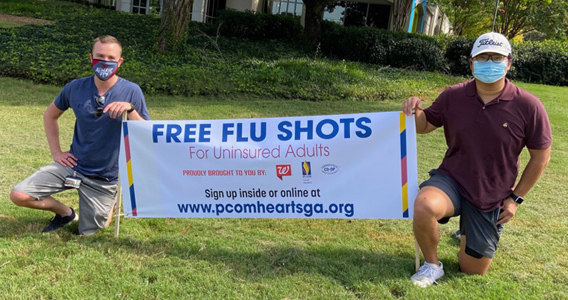 Two PCOM Georgia medical students wearing face masks kneel in front of a health clinic and hold a large banner promoting free flu shots for uninsured adults