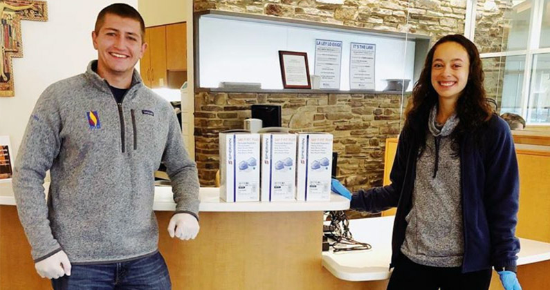 Two PCOM medical students smile as they deliver boxes of new protective face masks to a healthcare center.