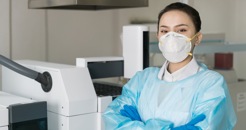 Female grad student wears protective gown, gloves and face mask inside a research laboratory.