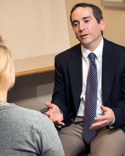 Dr. Scott Glassman counsels a patient in an office