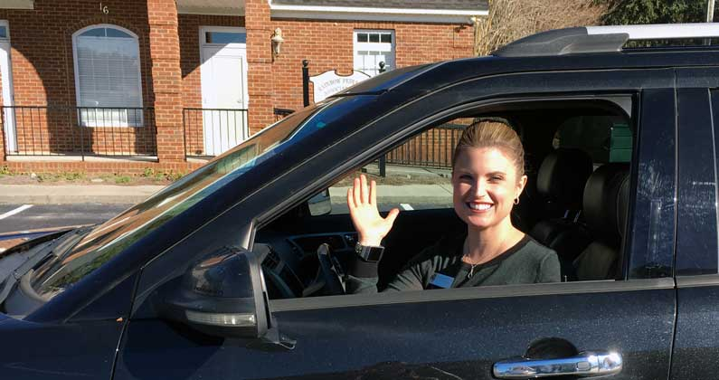 Assistant Director of Admissions Dana Brooks waves from her car.