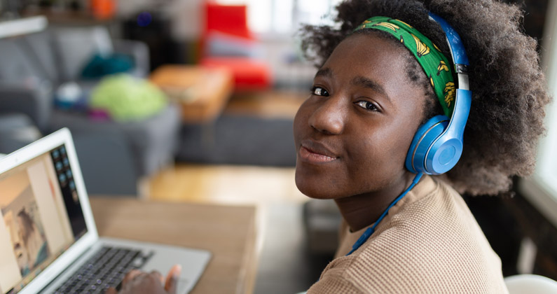 High school student wears headphones and uses a laptop for online learning in her home