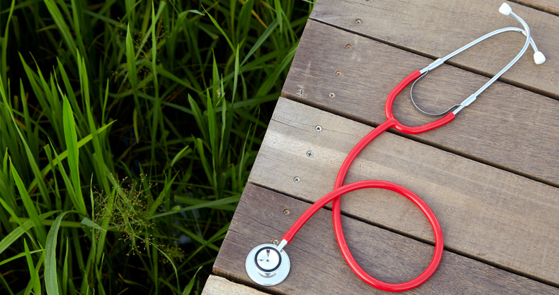 A stethoscope sits on a wood plank walkway on top of a green grass field.