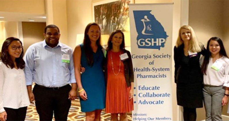 PCOM Georgia pharmacy students and faculty smile in front of the GSHP Summer Meeting conference sign.