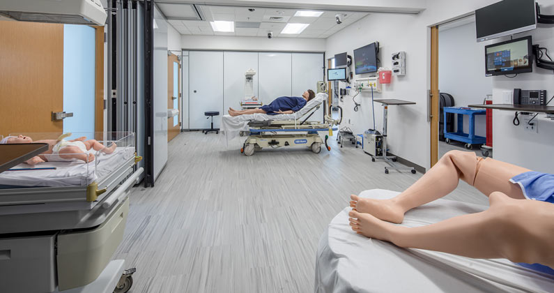 Mannequins, hospital beds and medical equipment in the birthing area of the Simulation Center